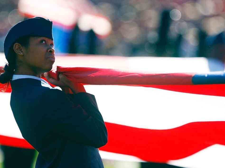 An ROTC member opens an American flag on the field prior to the start of a football game.