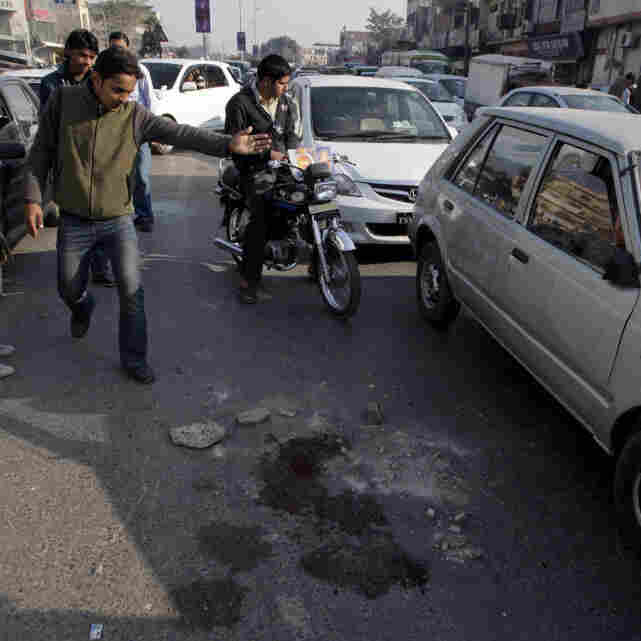 Blood stained the street in Lahore, Pakistan, where police say an American shot and killed two armed men Thursday.