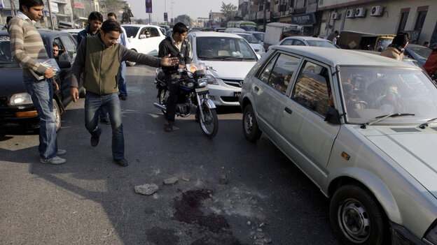 People look at blood stains on the road in Lahore, Pakistan, today (Jan. 27, 2011), where an American shot and killed two Pakistanis.