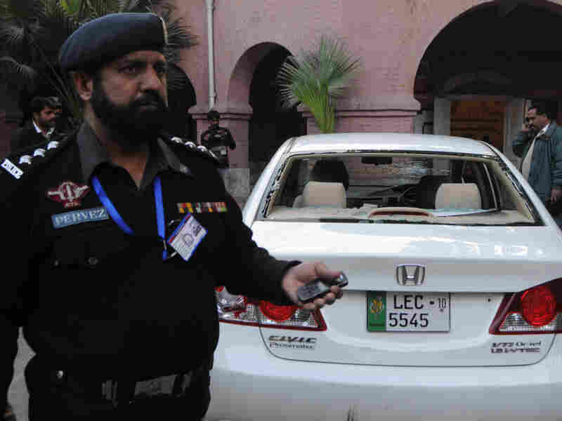 Policemen gathered around the car of a U.S. consulate worker at the police station in Lahore.
