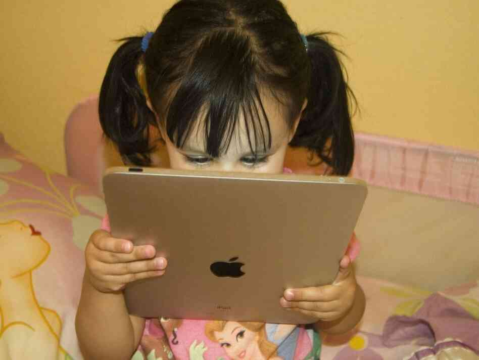 Lily Gallaga reading on an iPad.