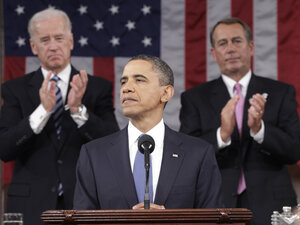 President Barack Obama is applauded by Vice President Joe Biden and