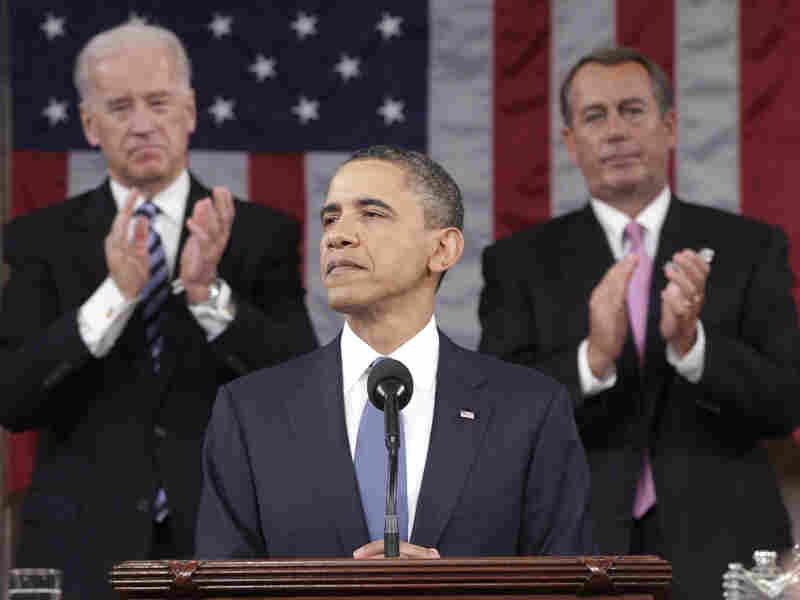 President Barack Obama is applauded by Vice President Joe Biden and Speaker of the House John Boehner while delivering his State of the Union address on Capitol Hill.