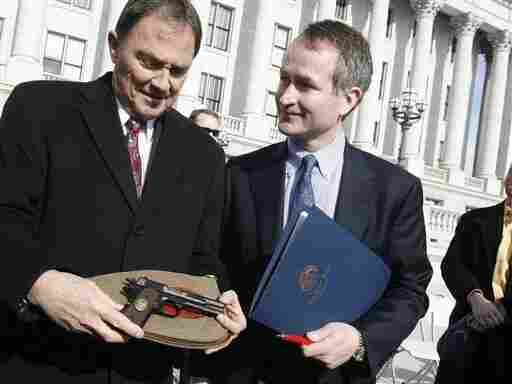 Utah Gov. Gary Herbert shows a Browning automatic pistol that was presented to him by Chris Browning [right], the great grandson of John M. Browning, who created the handgun, on John M. Browning Day in Salt Lake City on Monday. This week, the Utah House voted to choose the Browning M1911 semiautomatic pistol as one of the state's symbols.