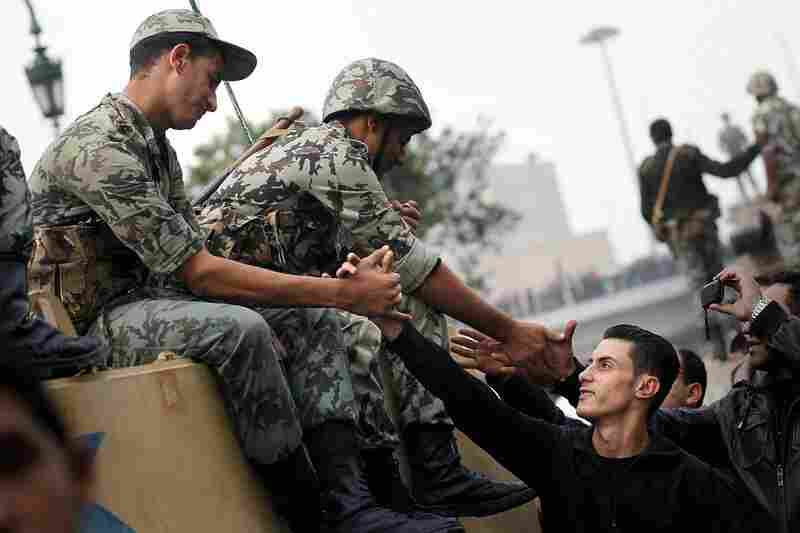 Protesters shake hands with Egyptian soldiers in Cairo on Saturday.