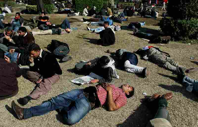 Exhausted Egyptians rest on the grass in in Cairo's Tahrir Square  on Sunday after days of protests.