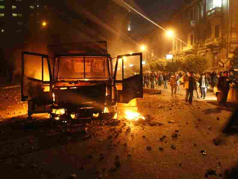 Egyptian demonstrators shout slogans next to a burning riot police vehicle in Cairo on January 28. Thousands of protesters have demonstrated against the government this week.