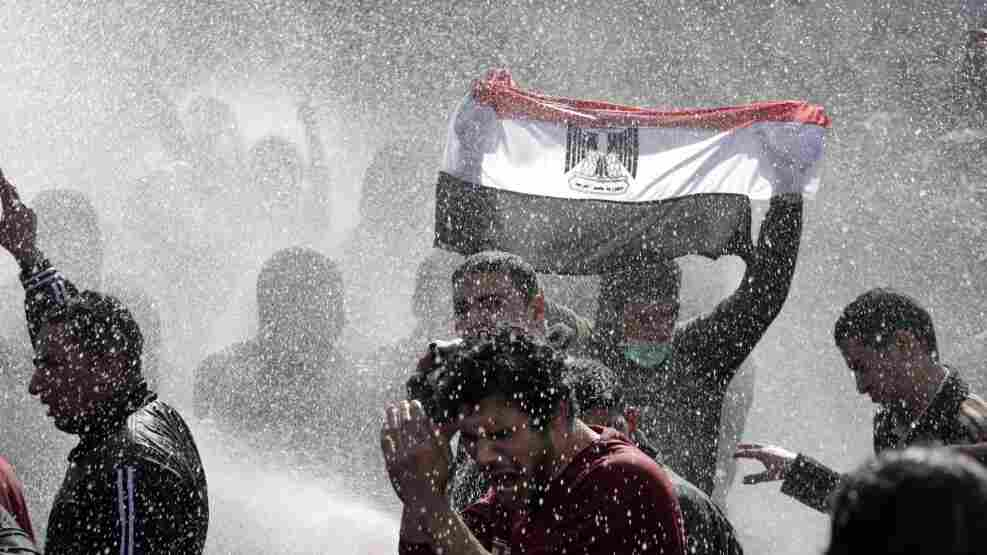 An Egyptian protester flashes Egypt's flag as anti-riot policemen use water canon against demonstrators in Cairo today (Jan. 28, 2011).