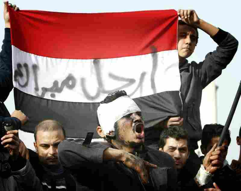 "Protesters hold an Egyptian flag with a slogan reading ""Mubarak go away"" in Cairo on Saturday."