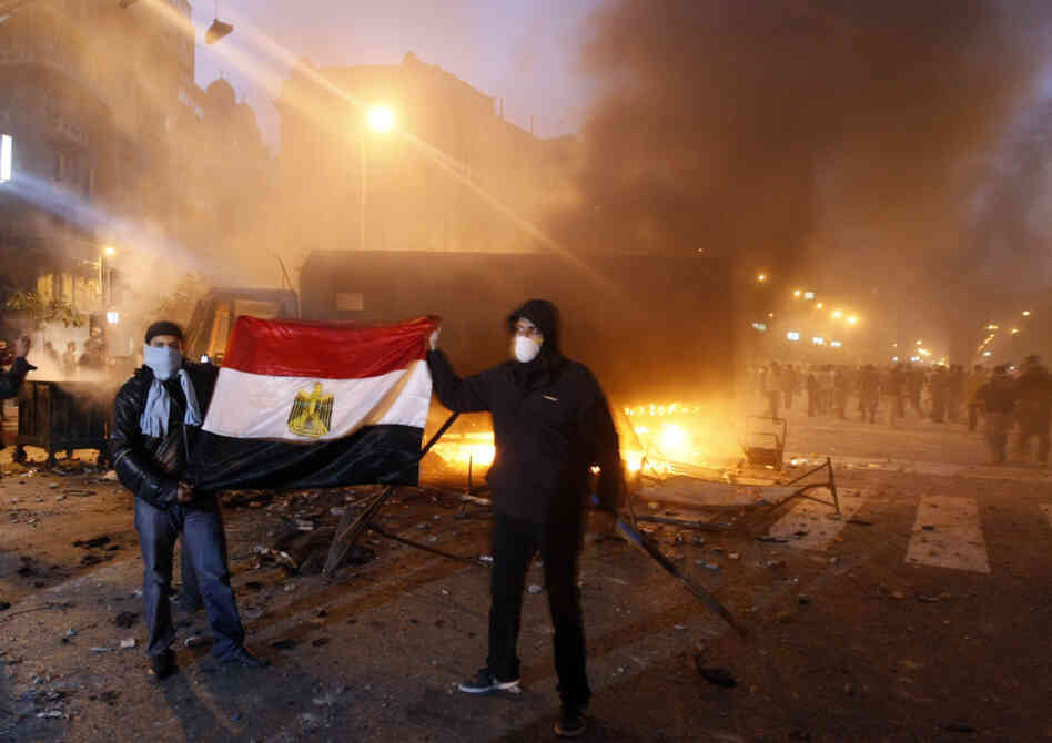 Demonstrators hold up the Egyptian flag as they stand next to a burning riot police vehicle in Cairo.