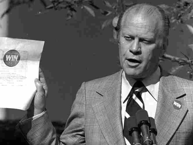 "President Ford holds up a WIN, or ""Whip Inflation Now,"" enlistment form, which asks citizens to sign up as inflation fighters during his news conference in the White House Rose Garden on Oct. 9, 1974. The slogan turned out to be a dud."