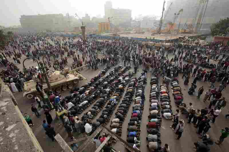 Demonstrators pray alongside an army tank in Cairo on Saturday.