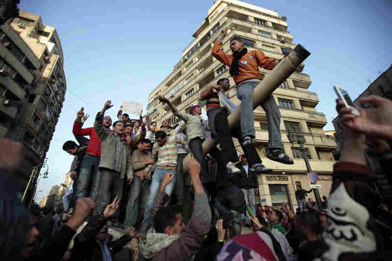 Protesters chant while atop an army tank in Cairo on Saturday.