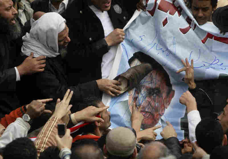 A protestor displays his disgust by putting a shoe against a portrait of Egyptian President Hosni Mubarak in Cairo on Sunday.