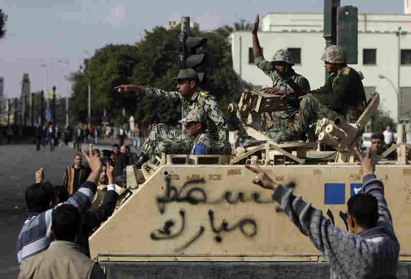"People gesture towards Egyptian soldiers aboard an armored personnel carrier emblazoned with the words ""Down Mubarak"", in Cairo on Sunday."
