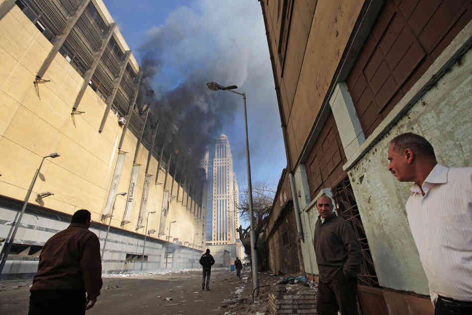 Egyptians watch smoke billow from a shopping center in Cairo on Sunday that was looted, damaged and set on fire overnight.