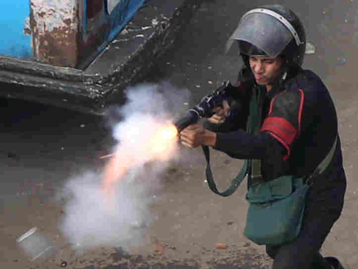 An Egyptian police officer fires tear gas at demonstrators in Cairo.