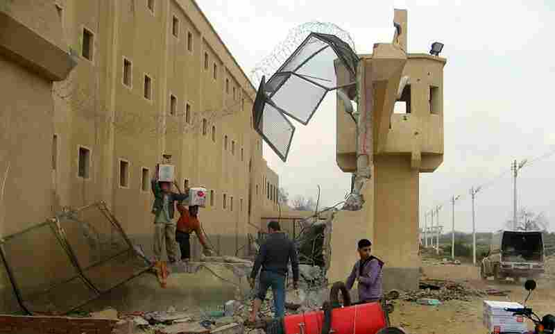 Looters pick outside Abu Zaabel prison in Cairo on Sunday after a mass breakout by convicts overnight.