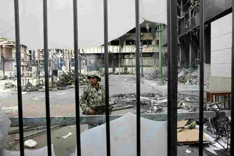 An Egyptian soldier stands guard near burnt buildings in Cairo on Sunday.