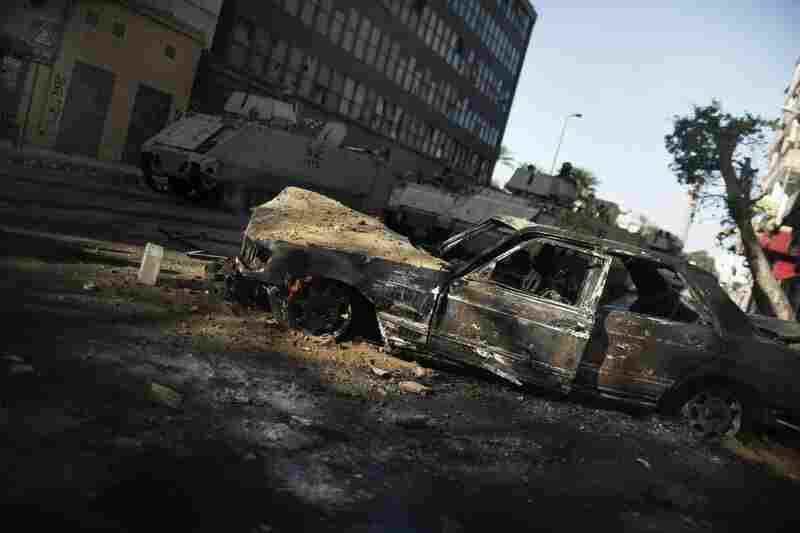 Armored personnel carriers pass behind a burned-out car near Tahrir square in Cairo on Sunday.