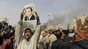 """Expressing his opinion: Earlier today in Cairo, this man held up a poster. The defaced photo of Egypt's president had the words """"Mubarak, get out"""" written on it."""