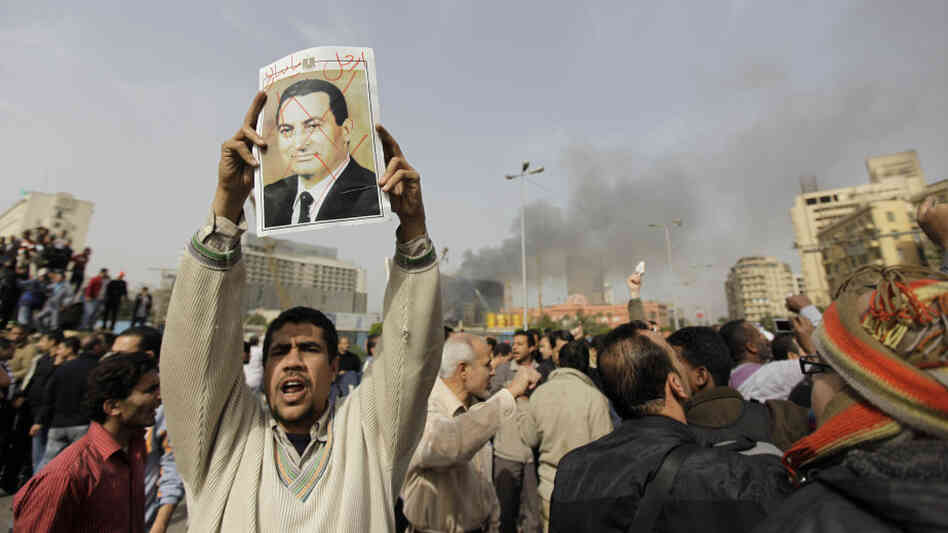 "Expressing his opinion: Earlier today in Cairo, this man held up a poster. The defaced photo of Egypt's president had the words ""Mubarak, get out"" written on it."