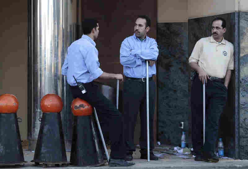 Egyptian men hold poles to ward off looters near a shopping center  in Cairo on Sunday.