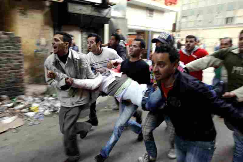 Egyptians carry an injured  protester during clashes with anti-riot police in Cairo on Saturday.