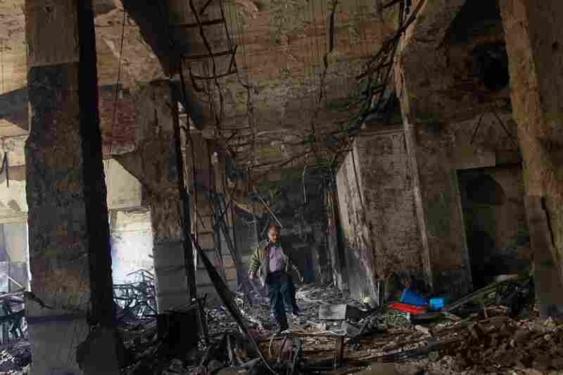A man walks through the charred remains of a burned government building in Cairo on Sunday.