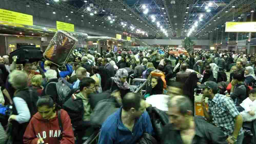 Passengers crowd the departures area at Cairo international airport on Sunday.