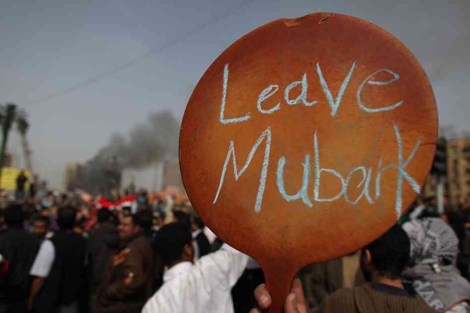 A protestor in Tahrir Square holds up a sign calling on President Mubarak to leave. Riot police and the army have been sent to quell the protests, which so far have claimed nearly 100 lives.