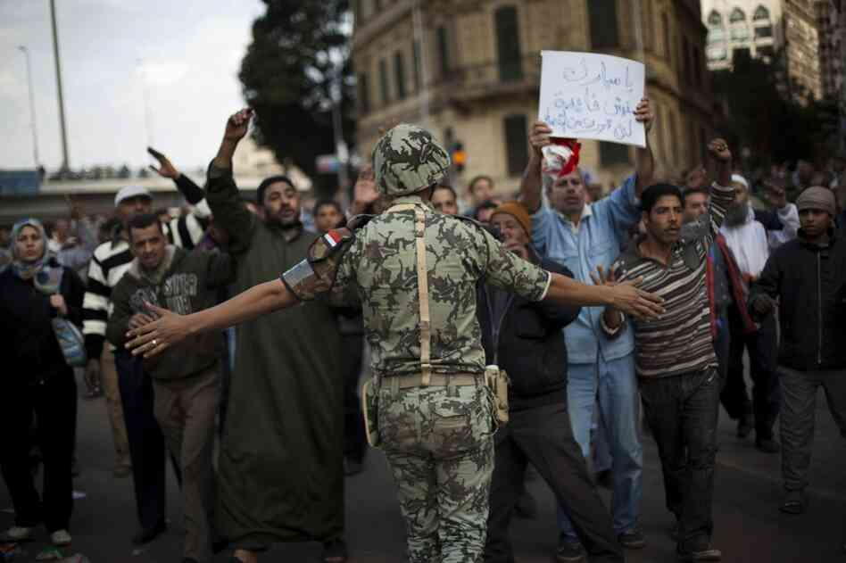 An Egyptian army soldier tries to stop anti-government protesters as they walk towards Tahrir Square on Sunday.