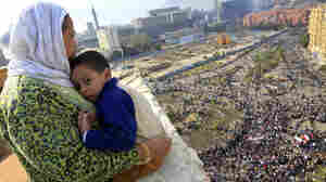 An Egyptian mother hugged her child as she watched thousands of Egyptian protesters gather at Tahrir square in Cairo earlier today (Jan. 30, 2011).