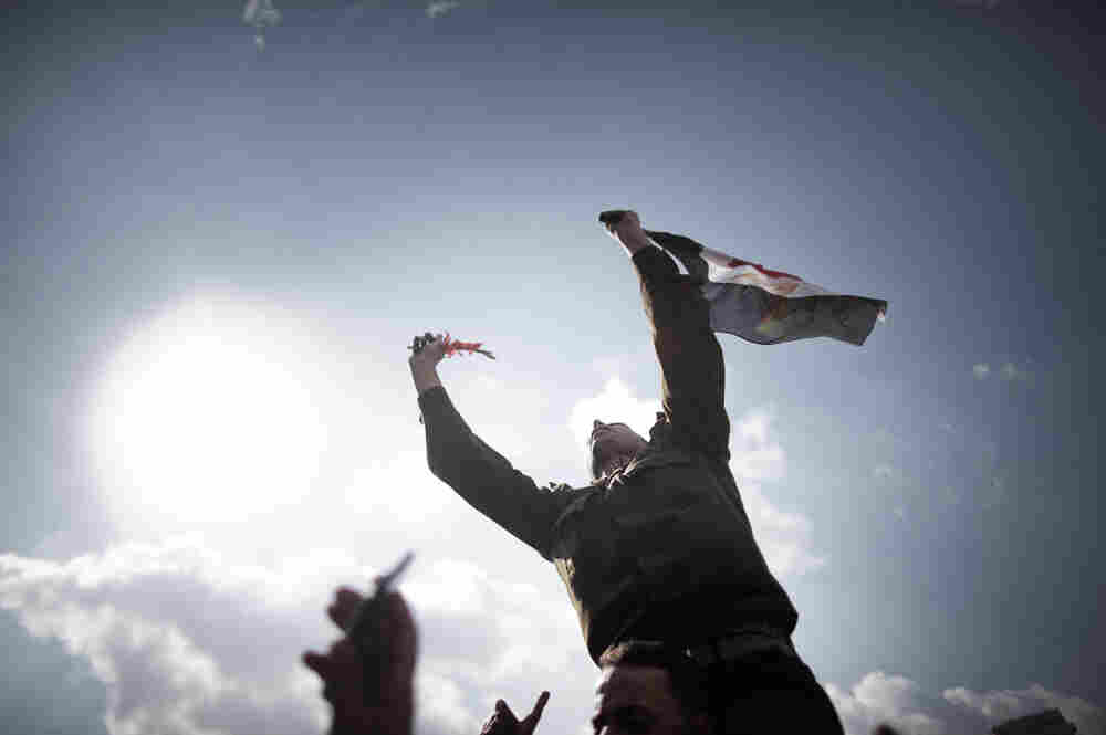 An Egyptian army Captain identified as Ihab Fathi holds the national flag while being carried by demonstrators during a protest in Tahrir Square in Cairo on the seventh day of mass protests calling for the removal of President Hosni Mubarak.