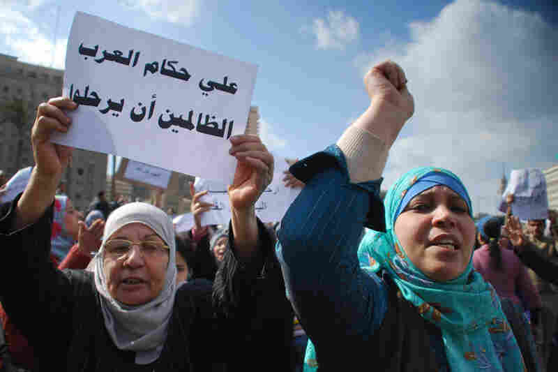 "Women, one holding a poster reading ""All Arab oppressors must leave,"" react during an anti-government demonstration in Cairo on Monday."