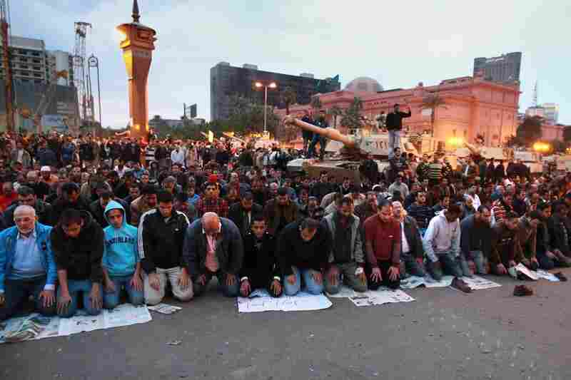 People pray in front of army tanks in Tahrir Square on Sunday, the sixth day of mass protests across the country calling for the resignation of long-term president, Hosni Mubarak.