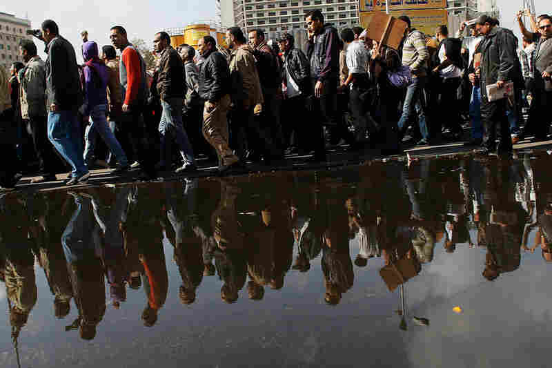 A crowd of anti-government protesters walks by a large puddle of water from tapped water mains in Tahrir Square on Monday.