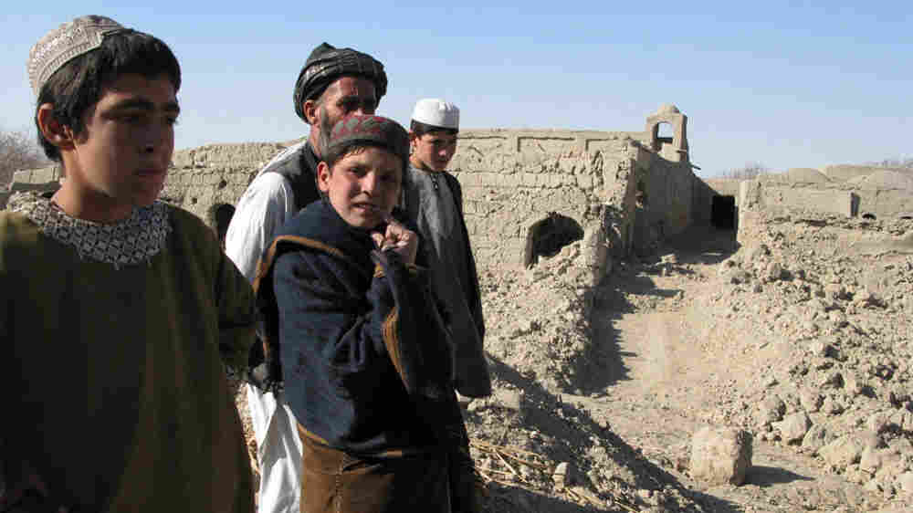 Children stand on the ruined wall of a house in a hamlet in Lower Khasro,  Arghandab.