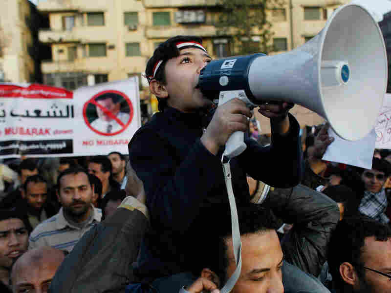 An Egyptian boy wields a megaphone as he chants anti-government slogans in Cairo's Tahrir Square on Monday afternoon.