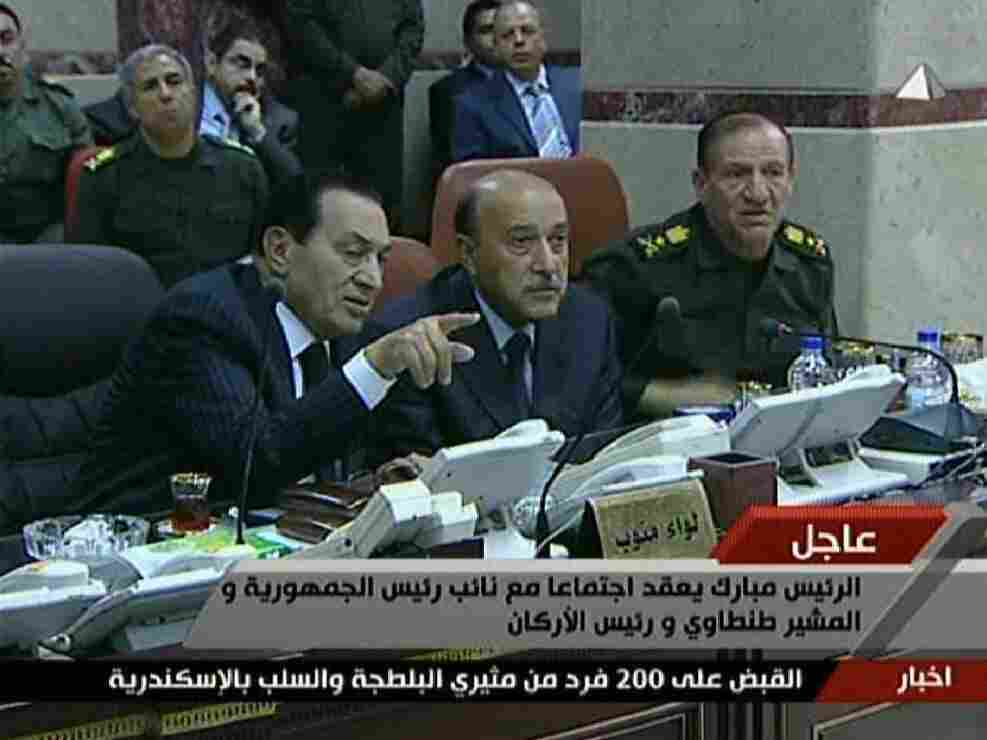 An image grab taken from Egyptian state television shows Egyptian President Hosni Mubarak (left) speaking with his new Vice President Omar Suleiman (center) and Chief of Staff Sami Anan during a visit to the military operations center in Cairo on Sunday.