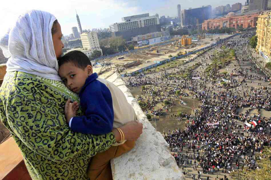 A woman hugs her child as she watches some thousands of protesters gather at Tahrir square. In the distance, the ruling National Democratic party building smolders behind the red-colored Egypt museum.