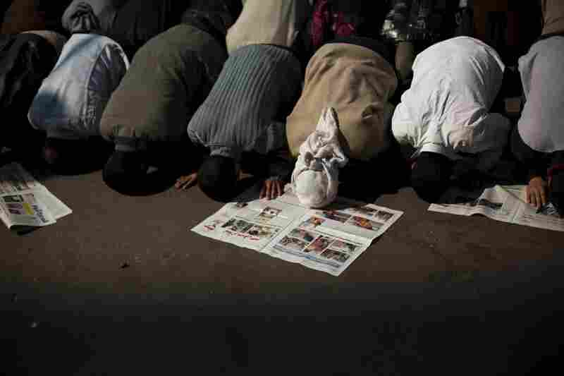 Anti-government protesters pray next to newspapers with the latest local news in Tahrir Square.