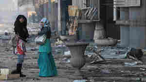 Women in Cairo walk past a shopping center Monday that was damaged during the anti-government uprising.