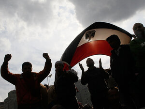 Protesters hold up an Egyptian flag and chant anti-government slogans during a protest in Tahrir Square in Cairo during an uprising that many are comparing to Iran circa 1978.