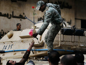 An Egyptian Army soldier is a handed a flower by an anti-government protesters in Tahrir Square in Cairo, Egypt.
