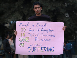 A man holds a placard in Tahrir Square in Cairo, Egypt. Cairo remains in a state of flux and marchers continue to protest in the streets, demanding the resignation of Egyptian president Hosni Mubarek.