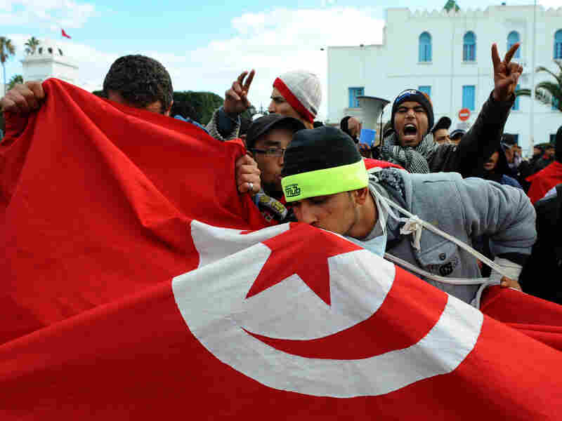 Tunisians kiss their country's flag during a demonstration in Tunis. Although the situation in Tunisia has calmed in comparison to Egypt, their revolution isn't over yet.