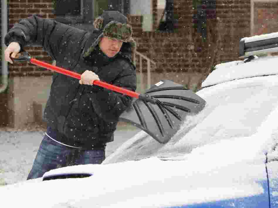 Tom Gillian uses a snow shovel to chip ice from his windshield in Denver on Monday. A monster winter storm is revving up in the Rockies and is expected to drop up to 2 feet of snow in some parts of the Midwest and an inch of ice in others.