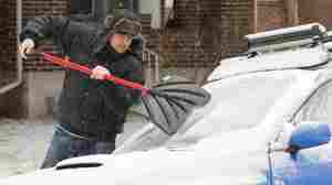 Tom Gillian uses a snow shovel to chip ice from his windshield in Denver on Monday. A monster winter storm is revving up in the Rockies an
