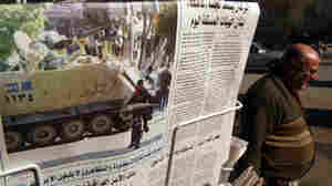 An Iraqi man walks past a stand showing a daily newspaper with an image from Egypt on the front page Tuesday.